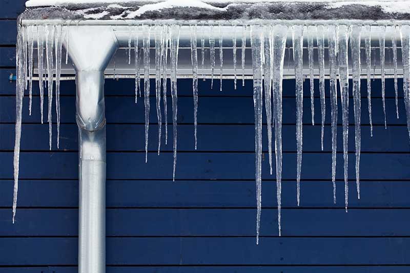 Eiszapfen hängen von den Regenrinnen