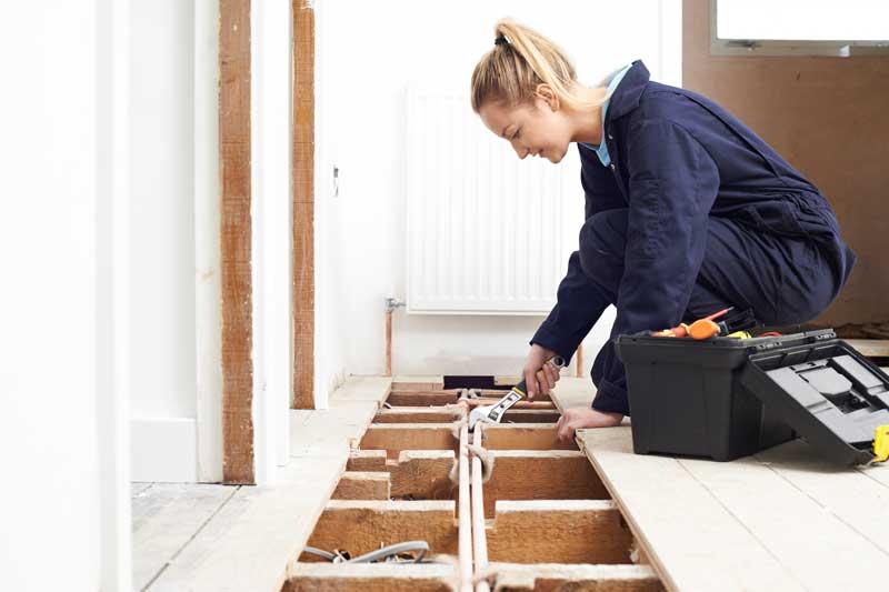 Frau repariert die heizung