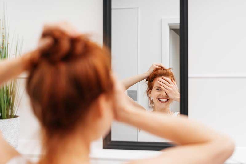Frau lächelt sich im Spiegel an
