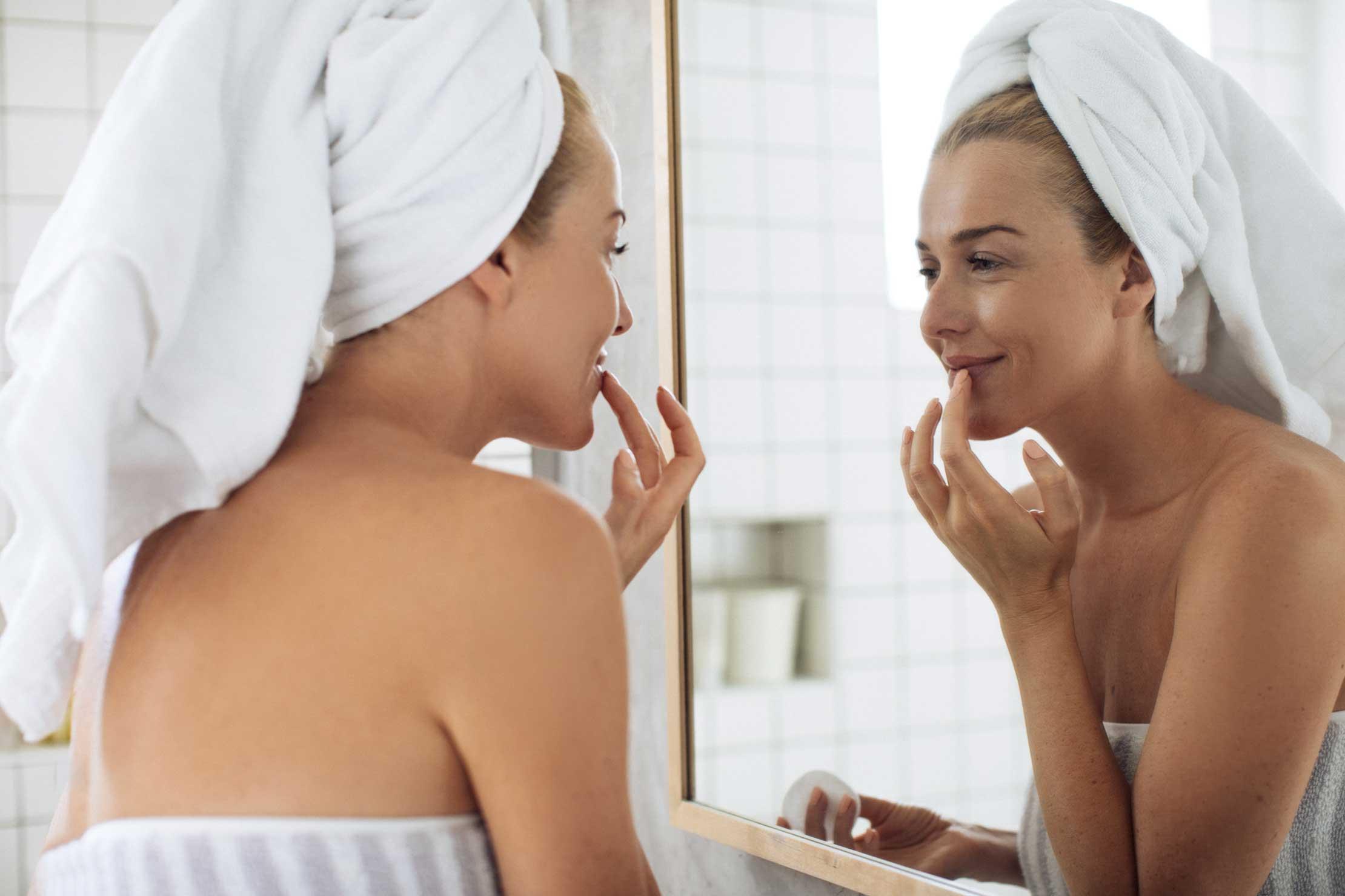 Frau mach sich vor Ihrem Badspiegel fertig