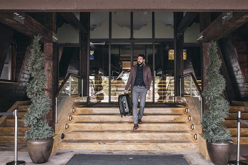 Mann verlässt den Hoteleingang und läuft mit seinem Koffer die Treppen runter