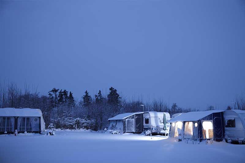 Campingplatz mit Wohnwägen im Schnee
