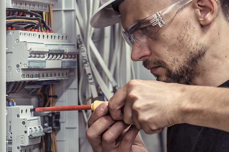 Elektroniker mit Schraubenzieher bei der Arbeit