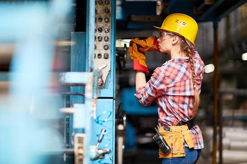 Mechatrokikerin mit gelbem Helm und Schraubenzieher bei der Arbeit