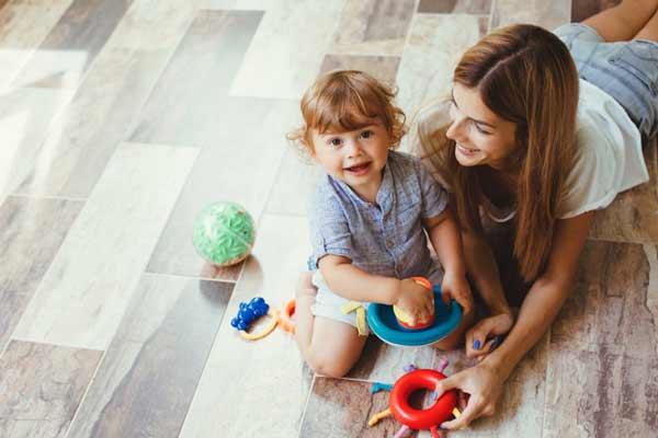 Mutter und Kind sitzen auf dem warmen Fußboden
