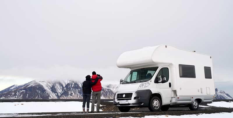 Wohnmobil vor einer Eisbergkette mit Pärchen nebendran