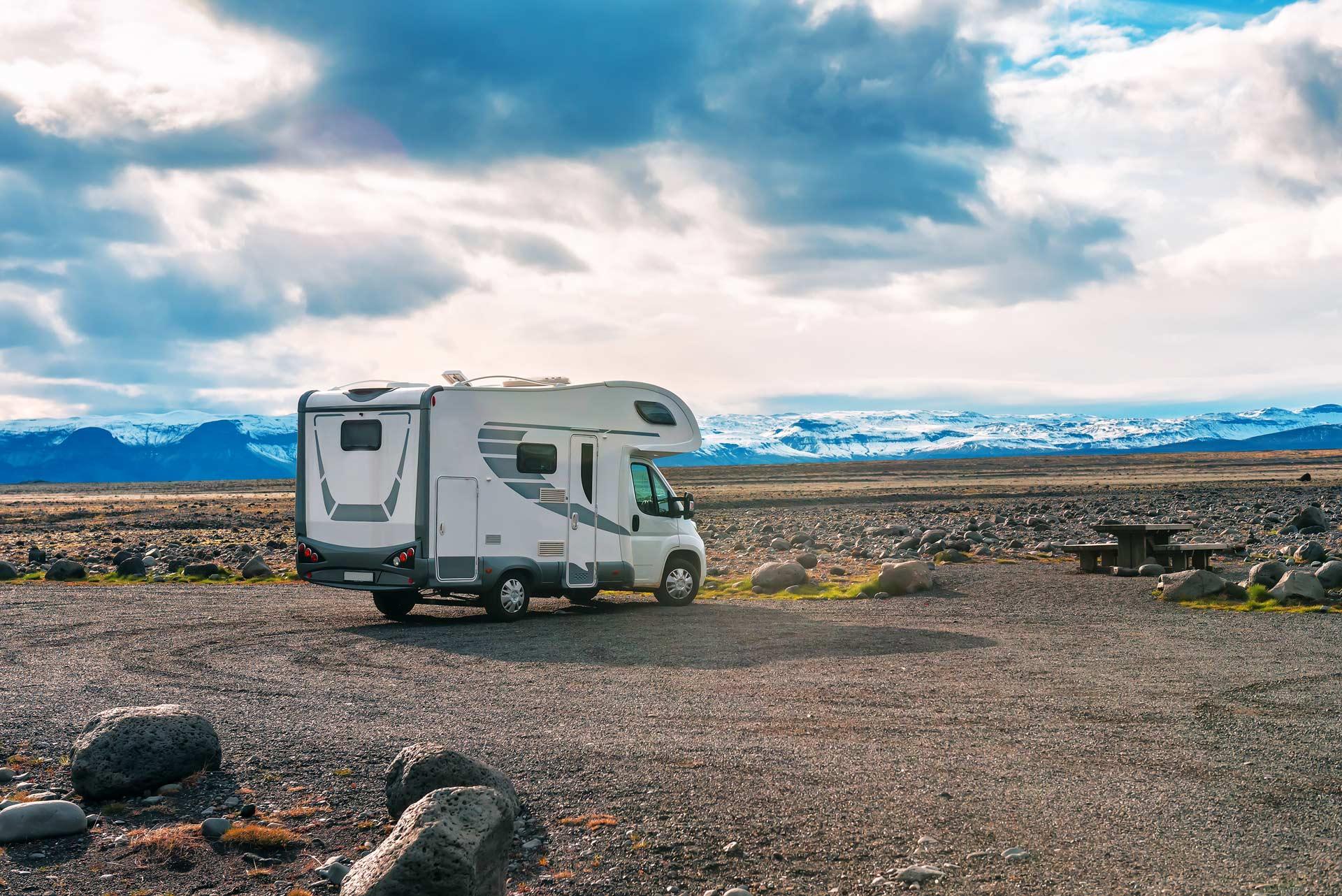 Wohnmobil vor einer Eisbergkette in Island